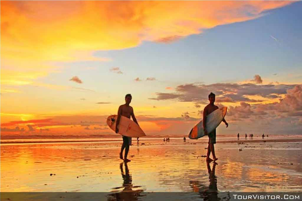 A surfer walking in Kuta beach on the sunset moment